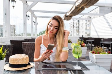 Beautiful summer girl in cafe, listens to music with headphones. On table is a cocktail, a tablet. Mobile phone, online application social networks. Happy smiling resting in a restaurant.