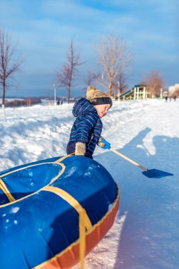 A little boy of 3 years old, in winter on street is dragging tubing, for riding from a hill, in the hands of a childrens paddle, playing, having fun, relaxing on weekends, background snow drifts.