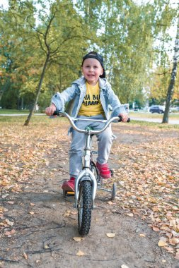 little boy, child 3-5 years old, smiles happy, laughs, rides bicycle, on summer spring autumn day in a city park, keeps his balance, rests on weekends, learns to ride bicycle training and dexterity.