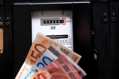 An electricity meter, electricity savings and euro banknotes