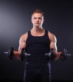 Fotografie Handsome muscular man working out with dumbbells