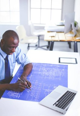 African american architect working with computer and blueprints in office