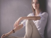 junge Frau sitzt auf dem Boden neben dunkler Wand