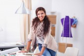 Young woman fashion designer working at studio.
