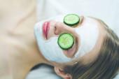 schöne junge Frau erhält Gesichtsmaske der Gurke in Schönheitssalon