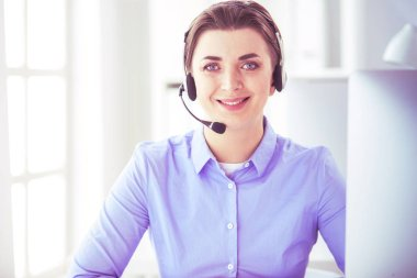 Serious pretty young woman working as support phone operator with headset in office. stock vector