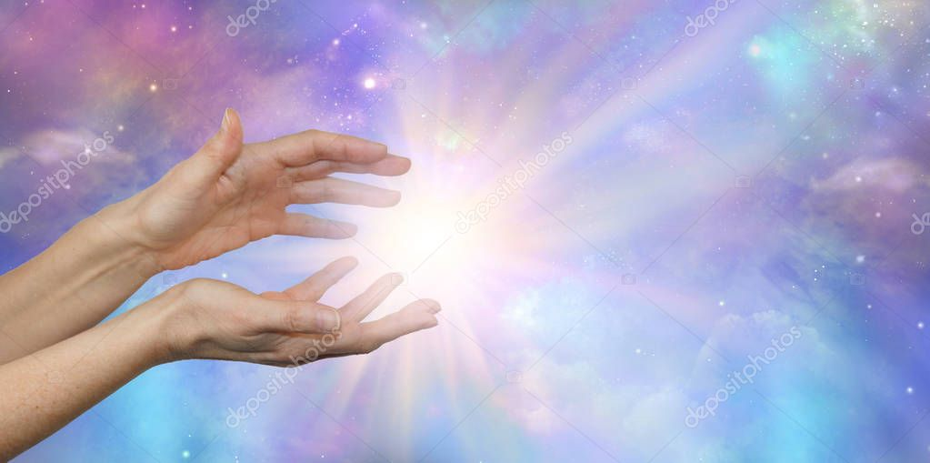 Cosmic Energy - female hands reaching into a bright white cosmic flash against a beautiful colourful night sky Universe background with copy space