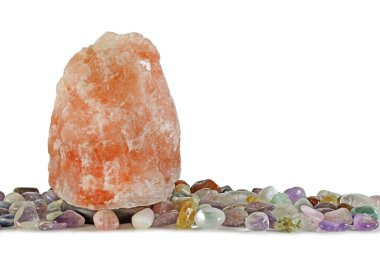 New Age Salt Lamp with Healing Crystal Selection - Large 10 kilo pink Himalayan Salt Lamp aligned with random collection of tumbled healing stones isolated on a white background with copy space