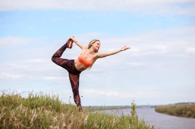 Woman is practicing yoga outdoors on the bank of river. Lord of the Dance pose.