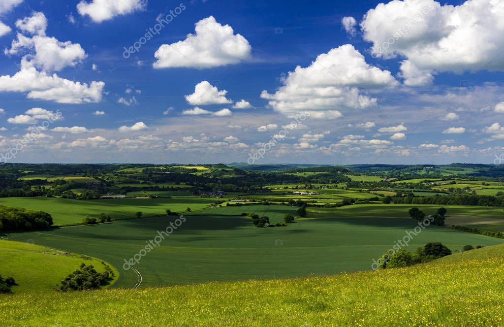 Bright sunlight warms the green crops and grassland of the Blackmore and Wardour Vales on the Dorset, Wiltshire and Somerset borders