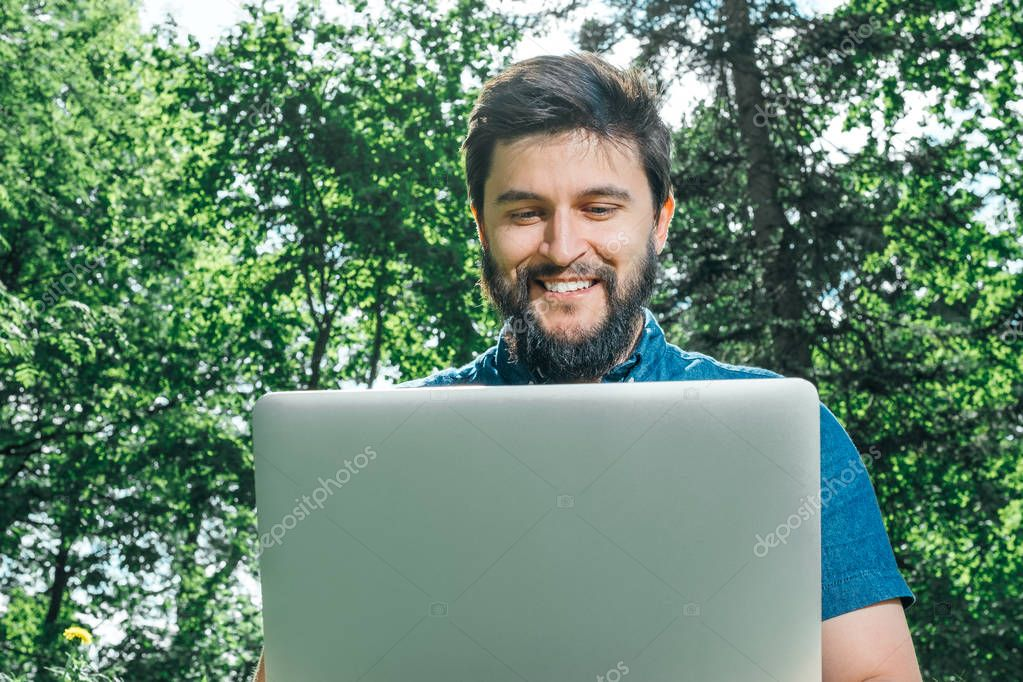Happy cheerful hipster man with a laptop sitting outdoors on green grass. Freedom  concept