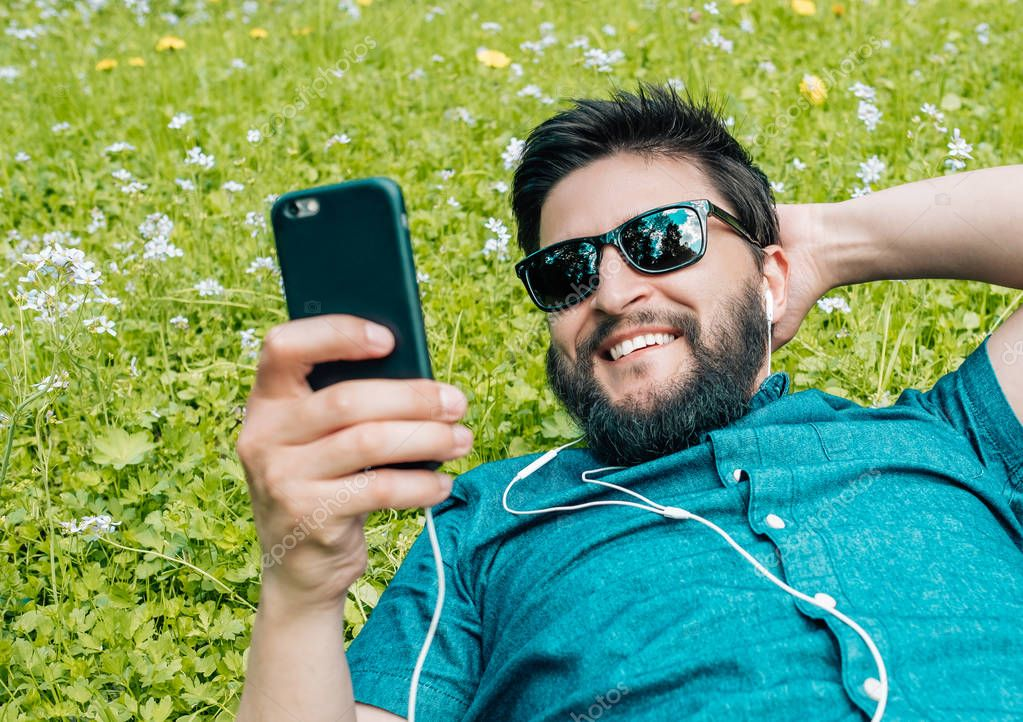 Portrait of a young happy man with a beard relaxing on the grass and using smartphone