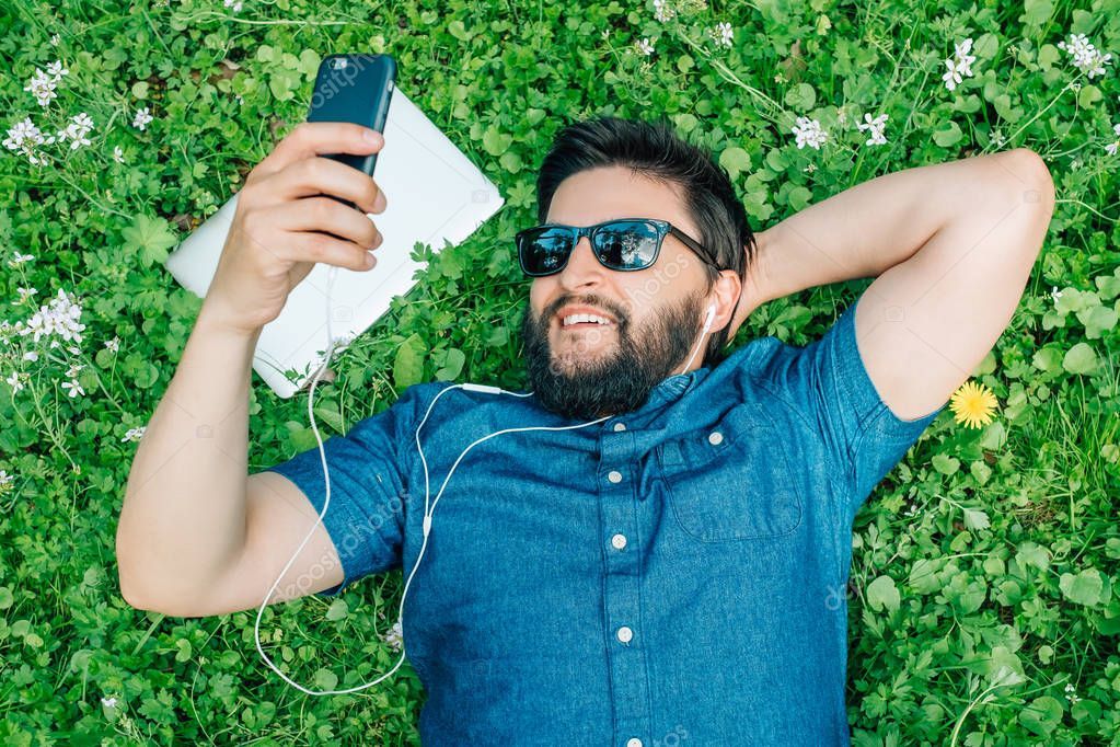 Handsome man lying on green grass in the park, listening music and using smartphone