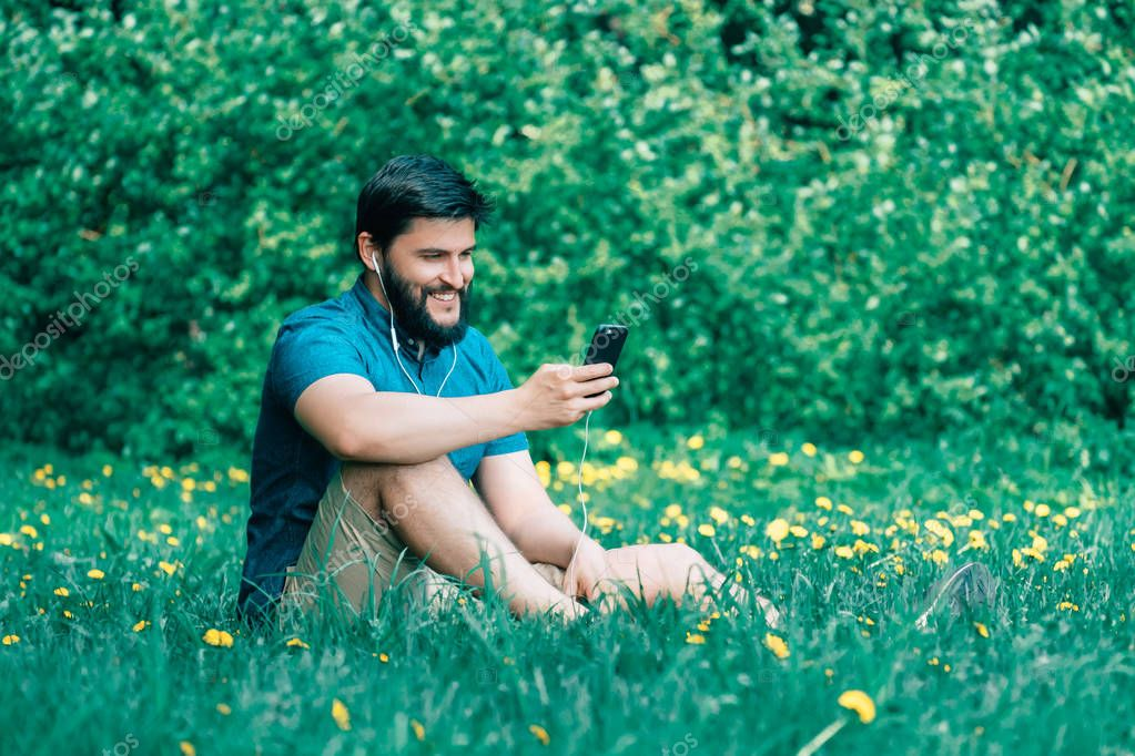 Young man sitting in the park and texting message. Smiling man on the grass using smartphone
