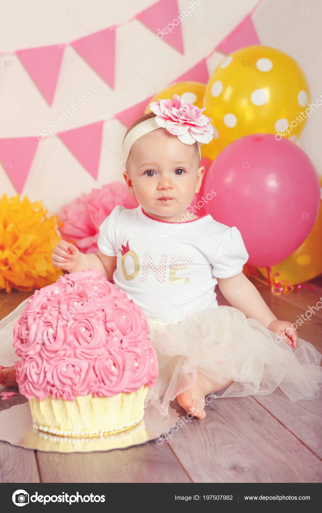 Portré a ravasz imádnivaló kaukázusi kislány tutu tüll szoknya ünnepli első  születésnapját. Torta smash koncepció. Gyermek gyerek ül a rózsaszín  zászlókkal ... 056e1938d4
