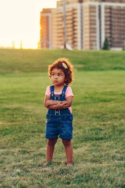 Loneliness of person. Portrait of cute adorable latin hispanic barefoot girl child in blue jeans romper standing in meadow park outside. Lonely scared baby got lost in big city.
