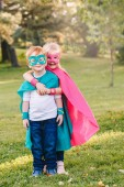Cute adorable preschool Caucasian children playing superheroes. Two kids friends hugging together outdoors in park. Happy active childhood and friendship concept.