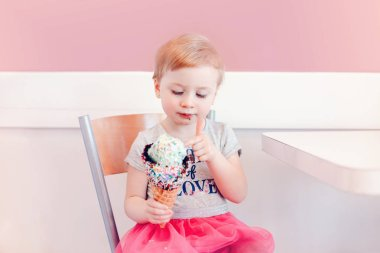 Cute adorable funny Caucasian blonde babyl girl child with blue eyes eating licking ice cream in large waffle cone with colorful sprinkles. Happy childhood lifestyle. Tasty summer food