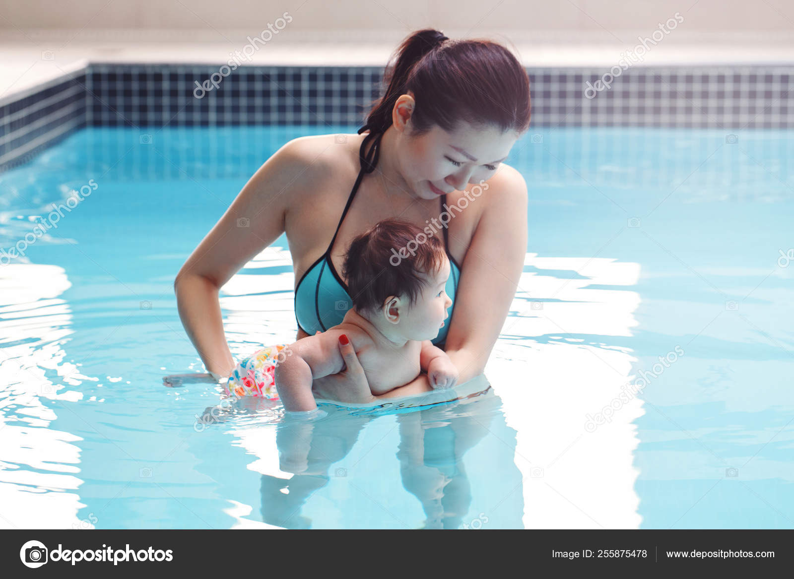 525fc606747 Mixed race asian mother training teaching her newborn baby to float in swimming  pool. Baby diving in water. Healthy active lifestyle.