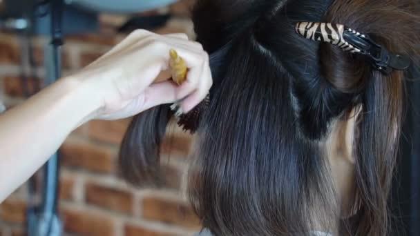 Detailní záběr ženy v kadeřnictví u holiče a sušení blond vlasy s fén a kulatý kartáč na vlasy.