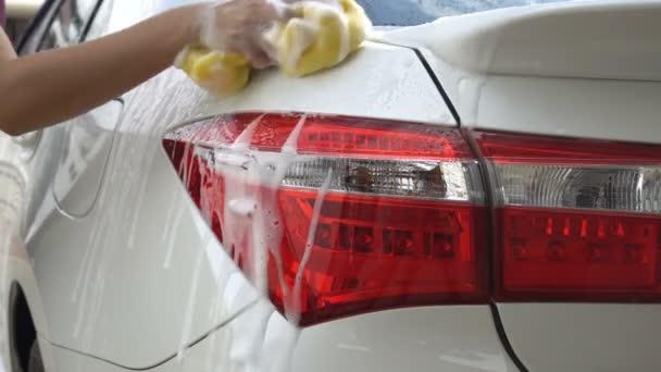 Uzavření ženské ručičky s čisticího automobilem ze žluté pěnové houbičky zadní světlo. Koncepce Autocar servis, mytí aut