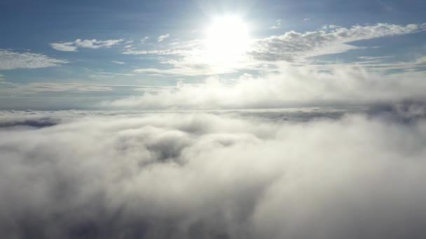 Letecký pohled letící nad mořem mraků se Sluncem.