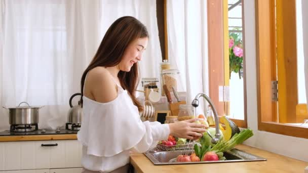 Cute asian woman wash vegetables and fruits to prepare for breakfast and look at camera and smiling brightly in kitchen.