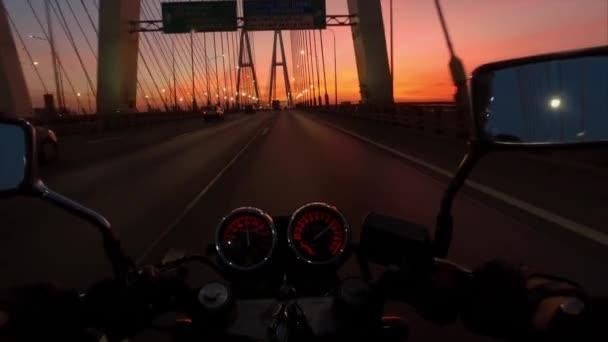 Motorkářská jízda na motorce jezdí na velkých brige v sunrise.
