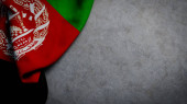 Flag of Afghanistan on concrete backdrop. Afghan flag background with copy space