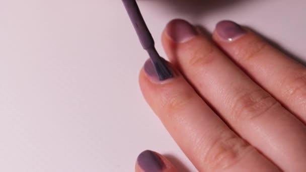 Dívka si sama lakuje nehty světle fialovým gelovým leskem. Manikúra doma.