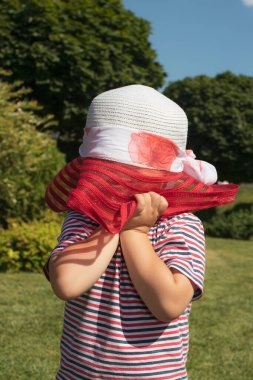 A 3-year-old boy in a red hat and a striped T-shirt. Happy childhood in the summer. Sun protection for children
