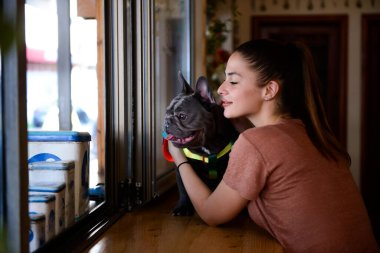 Young girl loving her cute Blue French Bulldog inside a small rustic pet friendly cafe