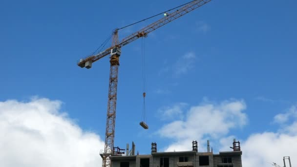 Ein Baukran bewegt Ladung beim Bau eines Hochhauses gegen einen wolkenverhangenen Himmel. Bau von Mehrfamilienhäusern