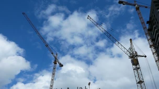 Zwei nicht funktionierende Baukräne vor blauem Himmel. Konzept zum Baustopp wegen Finanzkrise.