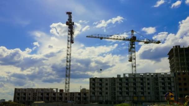 Proti zatažené obloze za slunečného dne, pracovní jeřáby při stavbě bytových domů ve velkém městě. Včasná