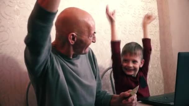 Junge und Großvater halten Kreditkarte in der Nähe des Laptop-Bildschirms und freuen sich über Lottogewinn