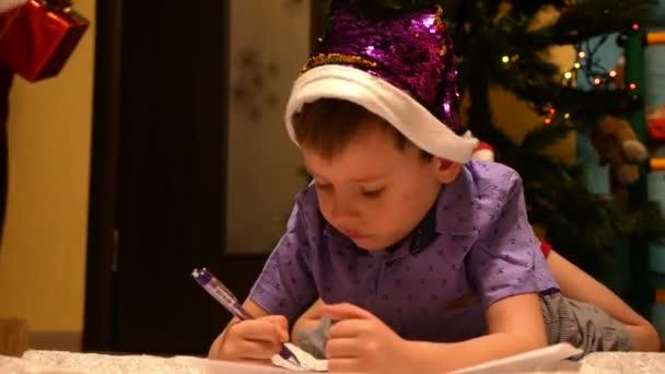 Ein süßer 4-6 jähriger kaukasischer Junge mit Weihnachtsmütze schreibt an Heiligabend einen Brief an den Weihnachtsmann im Hintergrund von einem geschmückten Baum, den der Weihnachtsmann mitbringt
