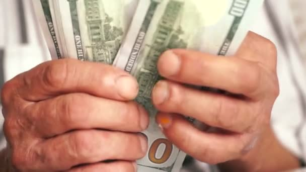 Close-up of an elderly mans hands holding American dollar bills.A pensioner is counting money, holding them in his hands.Home budget and savings. Selective focus