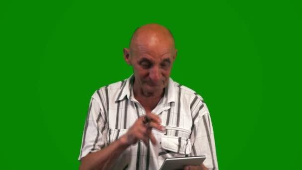 Ein fröhlicher kaukasischer Rentner mit rauchender Pfeife bedient sich eines mobilen Geräts auf grünem Hintergrund. Ein älterer verspielter Mann mit einem Tablet-Computer in der Hand. Grüner Bildschirm