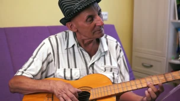 Elderly retired man in a gallant hat sitting at home on the couch plays an old acoustic guitar, musical leisure of an elderly man.Selective focus, shallow depth of field