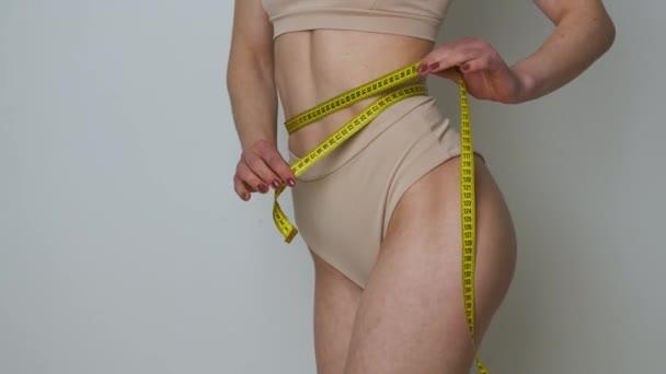 Portrét štíhlé dívky v hnědém spodním prádle, která měří její pas s páskou opatření po dietě nebo cvičení