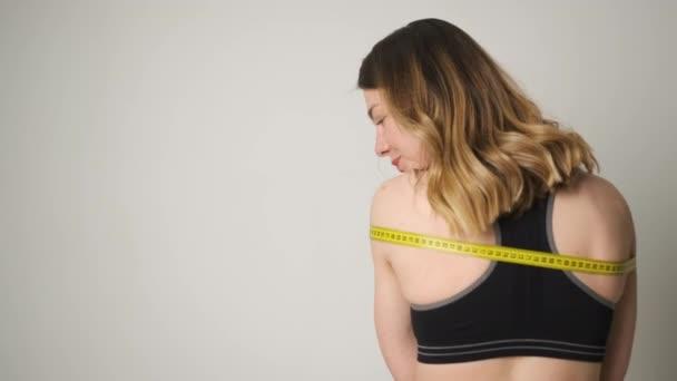 Portrét štíhlé dívky ve sportovním oblečení, která měří tělo pomocí pásky opatření po cvičení a šťastný s výsledkem