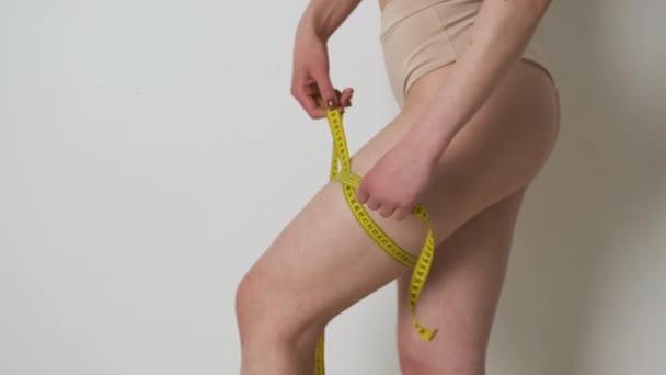 Portrét štíhlé dívky v hnědém spodním prádle, která měří nohu s páskou opatření po dietě nebo cvičení