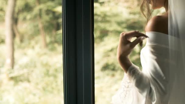 Krásná nevěsta ve svatebním závoji a župan sedí u panoramatického okna a čeká na svého prince. Okouzlená brunetka s bělošským vzhledem. Krásná svatba