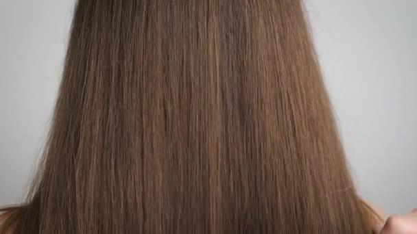 Egy 25 éves barna nő áll a fürdőszobában a tükör előtt, és fésüli a karcsú haját. Hajápolás