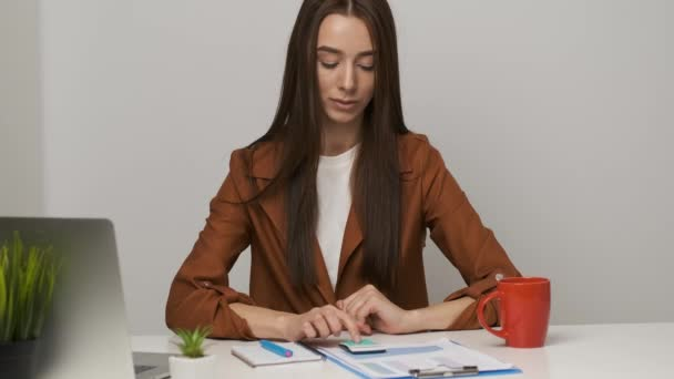 Brunette accountant girl sitting at the desk counts in the conciliator and writes in a notebook
