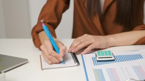 Bruneta účetní dívka sedí za stolem počítá do smírce a píše do zápisníku