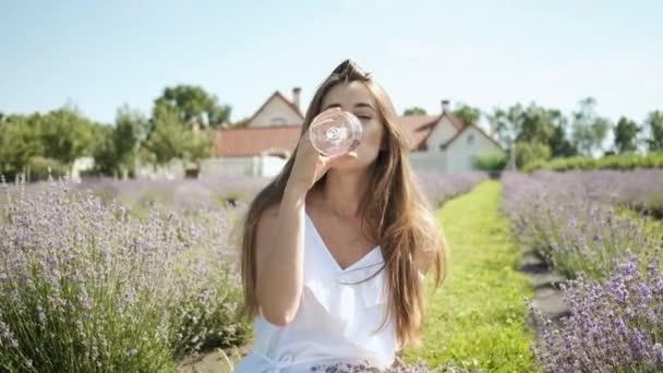 Krásná brunetka dívka v bílých šatech sedí v levandulovém poli a pije sklenici bílého vína těší květiny. Relax
