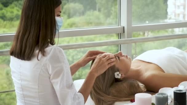Žena v masáži masíruje pacienty a míří do moderních lázní s panoramatickými okny. Zdraví a sebepéče. Relaxace