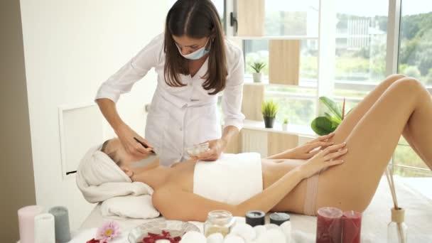 Žena ležící na stole na lázeňské procedury. Naneste masku na omlazení pokožky. Zdraví a krása
